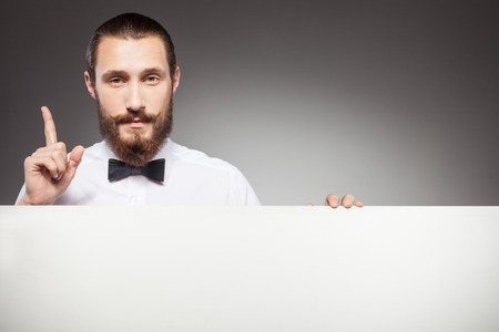 seriousness: Attractive bearded hipster guy is presenting white empty placard. He is standing and pointing finger up with seriousness. Isolated on grey background Stock Photo