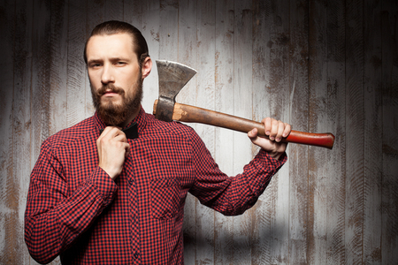 hatchet man: Attractive lumberjack with beard is holding a hatchet. He is standing and adjusting the bow-tie on his neck. The man is looking at the camera self-confidently. Copy space in right side Stock Photo