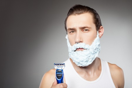 hesitation: Handsome bearded man is applying shaving foam on his face. He is holding a razor. The man is looking at the camera with hesitation. Isolated on grey background and copy space in left side
