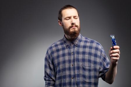 Enthousiaste homme avec une barbe ne veut pas se raser. Il tient un rasoir et regardant avec doute. L'homme est debout en chemise. Isolé sur fond noir et copier l'espace dans le côté gauche