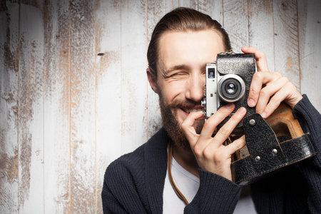 caras: Attractive bearded man is photographing with interest. He is holding camera near his eye and smiling. The guy is standing near wall. Copy space in left side