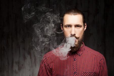 잘 생긴 수염을 기른 남자가 서 연기를 호흡한다. 그는 심각하게 기대하고있다. 왼쪽 공간을 복사
