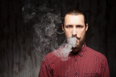 Handsome bearded man is standing and breathing out smoke. He is looking forward seriously. Copy space in left side Stock Photo