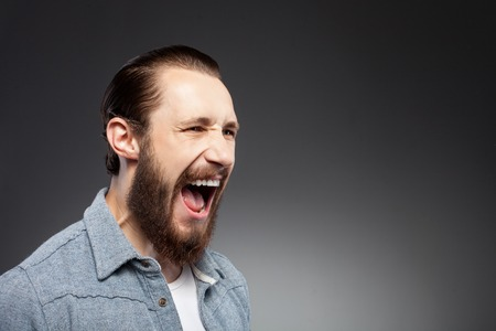 negatively: Attractive bearded hipster guy is showing his aggression. He is screaming negatively. The guy is standing and looking aside with irritation. Isolated on black background and copy space in right side
