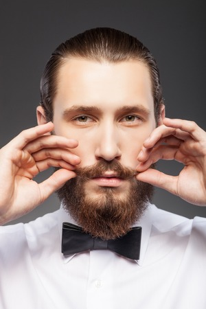 bigote: Hombre atractivo con barba se est� preparando para la reuni�n. �l est� de pie y el ajuste de su bigote. El hombre est� mirando hacia adelante con seriedad. Aislado sobre fondo negro Foto de archivo