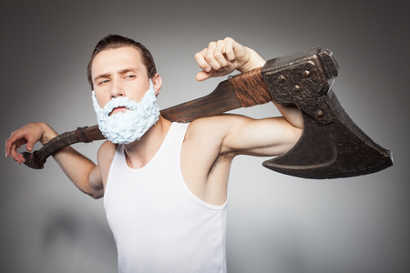 hatchet man: Attractive bearded man is holding hatchet. He has shaving foam over his beard. The man is standing with confidence. Isolated on grey background