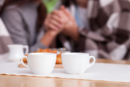 tea table: Close up of arms of man and woman holding hands with love. They are sitting in warm quilt in outdoors. There are two cups of coffee and croissants on the table. Focus on food