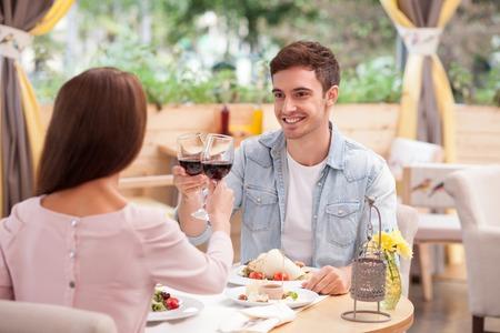 jovenes enamorados: Alegre joven y la mujer están saliendo en el restaurante. Están sentados en la mesa y mirando el uno al otro con amor. Los amantes están bebiendo el vino y sonriente. El hombre está dando un brindis Foto de archivo