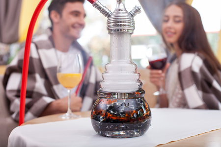steam mouth: Attractive man and woman are smoking hookah in cafe. They are sitting at the table and drinking cocktails. The boyfriend and girlfriend are smiling. They are warming with quilt