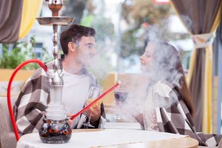 smoking pipe: Cheerful young loving couple is drinking wine in cafe. They are sitting and smoking hookah with pleasure. The man and woman are looking at each other with love. They are smiling Stock Photo