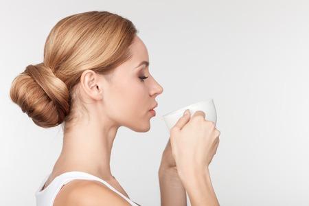 profil: Atrakcyjna zdrowa blond dziewczyna pije kawę. Ona stoi w profilu. Pani zamknęła oczy z przyjemności. Odizolowane i kopia miejsca na prawej stronie