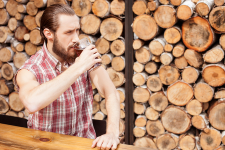 seriousness: Attractive bearded man is drinking beer in bar. He is sitting at the table. The man is looking forward with seriousness. Copy space in right side Stock Photo