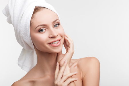 nude young woman: Beautiful healthy woman is satisfied with her body. She is standing with towel on her head and smiling. The lady is touching face and looking at camera happily. Isolated