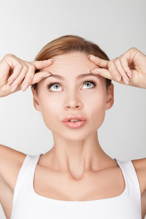 Beautiful healthy woman is touching and wrinkling her forehead. She is looking up at wrinkles with disappointment. Isolated on background Stock Photo