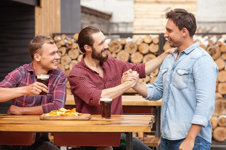 male       hand: Handsome two men are sitting and drinking beer in pub. Their friend is standing near them and shaking male hand. They are smiling and looking at each other happily
