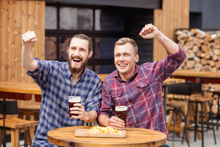 they are watching: Attractive young men are watching sport game in pub. They sitting at the table and drinking beer. The guys are raising fists up with aspirations. They are smiling