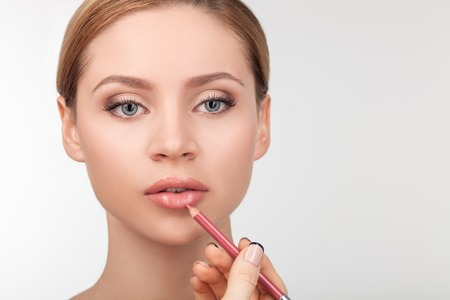 look make: Cheerful healthy woman is getting make-up. The female arm of visagiste is holding pencil and applying it on lips. The lady is looking forward with concentration. Isolated and copy space in right side