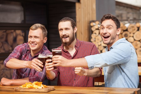 they are watching: Handsome men are watching football game in the pub with interest. They are drinking bear and laughing. The friends are sitting and clinking glasses Stock Photo