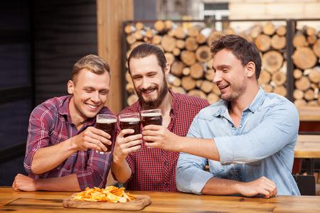 borracho: los hombres j�venes alegres est�n bebiendo cerveza es bar. Ellos est�n sentados en los vasos de mesa y tintinean. Los individuos est�n mirando a las bebidas con alegr�a y la sonrisa. Son felices y bebido