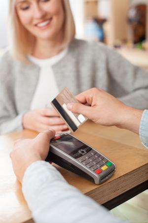 pagando: Cerca de las manos de barista que sirven al cliente femenina. La mujer está pagando por su pedido con tarjeta de crédito. Ella está sonriendo y tomando café. El cajero está de pie en la barra y que sostiene la tarjeta