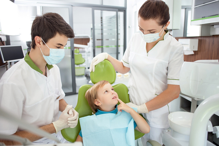 complaining: Cute boy is complaining of toothache. He is sitting in dental chair and pointing finger at tooth. He is looking at woman with hope. The dental doctor and assistant are listening to him attentively Stock Photo