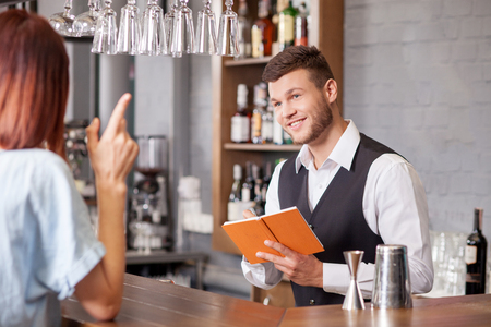 Handsome young barman is receiving order from woman. He is holding note-book and writing down her order. The man is listening to woman attentively and smiling. The lady is gesturing