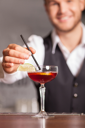 cocktails: Close up of professional bartender mixing cocktail with tubule. The man is standing and smiling in pub. Focus on glass of drink