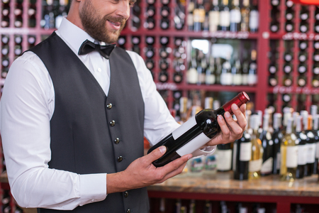 Close up of young sommelier holding a bottle of red wine. He is standing in cellar and smiling. The man is looking at alcohol drink with desire Stock Photo