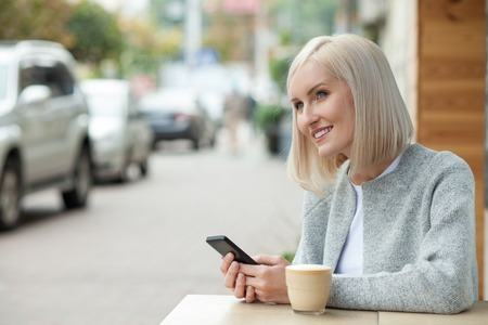 lady on phone: Attractive young girl is drinking latte in cafeteria. She is holding mobile phone and messaging. The lady is sitting outdoors and smiling. Copy space in left side