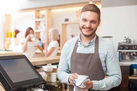 Atractiva propietario de la cafetería está sosteniendo una taza y secar con una toalla. Él está de pie y mirando a la cámara con alegría. El hombre está sonriendo. Dos mujeres están hablando y beber café en el fondo