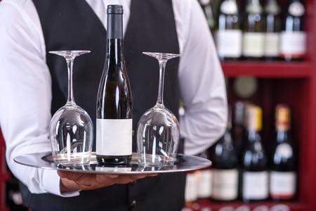 camarero: Cerca de las manos del camarero vino. �l est� sosteniendo una bandeja con una botella de vino y dos copas. El hombre est� de pie en el restaurante