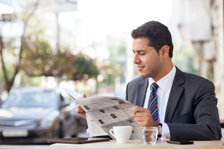 Attractive man in suit is sitting at table in cafe outdoors. He is reading newspaper with interest and smiling. The worker is drinking tea. Copy space in left side