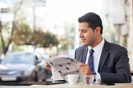 traje formal: Hombre atractivo en el juego que está sentado a la mesa en la cafetería al aire libre. Él está leyendo el periódico con interés y sonriendo. El trabajador está bebiendo té. Copiar espacio en el lado izquierdo