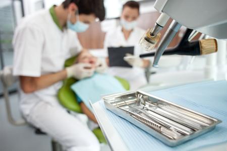 cadeira: Hábil dentista está examinando os dentes da criança. O homem e seu assistente feminina está sentado perto de um menino com concentração. A mulher está segurando pasta de documentos. Concentre-se no conjunto de ferramentas médicas Imagens