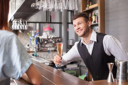 bar drinks: Attractive male bartender is serving woman. He is standing and giving her a cocktail. The man is looking at lady and smiling Stock Photo