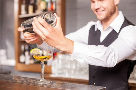 Handsome bartender is making cocktail in bar. He is holding shaker and poring beverage into glass. The man is looking at cocktail with inspiration. He is standing and smiling