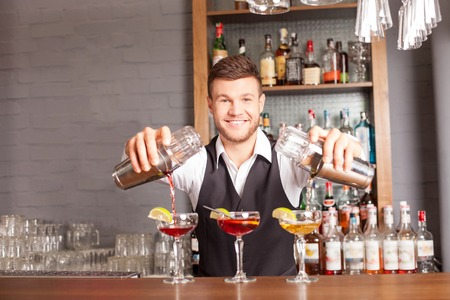 Attractive young bartender is preparing cocktails in pub. He is standing and holding two shakers. The man is pouring mixed drink into glasses. He is looking at camera and smiling