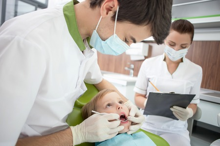 Cheerful young dentist is examining teeth of small patient. He is holding tools and looking a child seriously. The boy is opening his mouth with efforts. The female assistant is writing notes 版權商用圖片