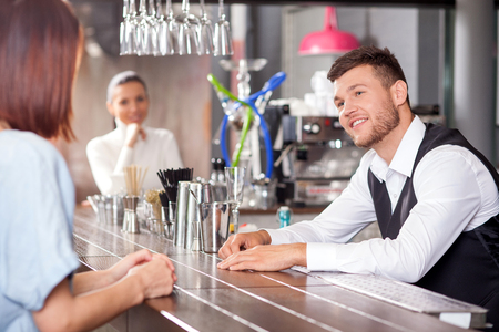 bartender: Cheerful bartender is standing at counter and talking with woman. He is looking at lady flirtingly and smiling. The women are sitting with joy