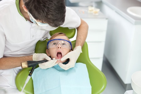 dentist mask: Skilled young dentist is drilling teeth of child carefully. The man is standing near kid with mask and gloves. The boy is sitting in chair and opening mouth with efforts. Copy space in right side
