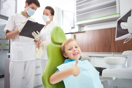 Pretty small boy is sitting in medical chair. He is giving thumb up and smiling. The dentist and female assistant are standing and discussing with seriousness. The man is writing documents Stock Photo