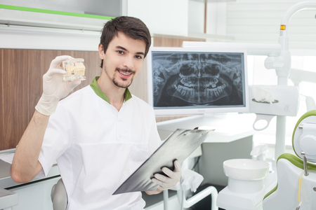 dentures: Attractive bearded dental doctor is sitting in his office. He is holding a folder of documents and smiling. The man is showing dentures and looking at camera happily Stock Photo