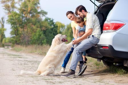 Mooie familie rust in het bos en het spelen met hond. Ze zitten op open kofferbak en omarmen. De man en vrouw met meisje glimlachen. Kopieer de ruimte op rechts Stockfoto