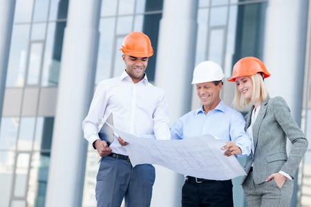man measurement: Professional young architects are discussing plan of building. They are wearing helmets and smiling. The foreman is standing and holding blueprint. The woman and man are looking there with interest