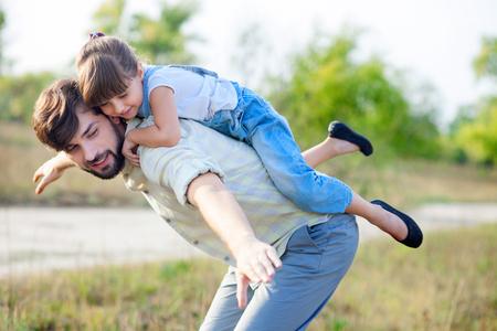 estiramientos: Hombre joven atractivo que está jugando con su hija en la naturaleza. El padre está de pie y llevando a chica en la espalda. Él es estirar los brazos hacia los lados. La familia está sonriendo Foto de archivo