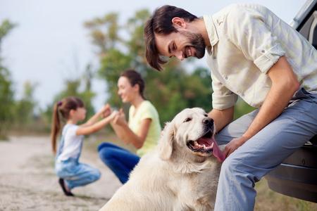 dog days: familiar Alegre está descansando en el parque. El hombre está jugando con el perro y apoyándose en coche. La madre y la hija están arrodillados y de la mano. Ellos están sonriendo