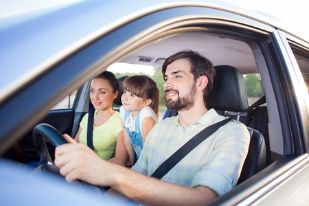 belts: Cheerful family is making trip by car. They are sitting and smiling. The man is driving transport with joy. The mother and girl are looking forward with happiness