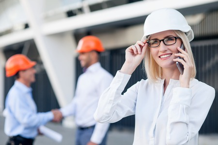 female architect: Attractive young female architect is talking on mobile phone with customer. The woman is smiling and adjusting eyeglasses. The builders are standing and shaking hands. Their project was approved