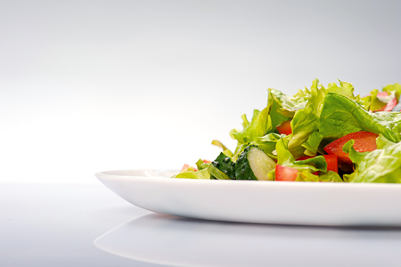 Close up of fresh salad of lettuce, cucumber and tomato on plate Isolated on blue background