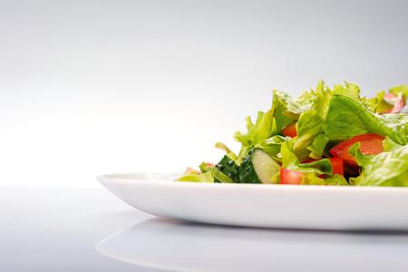 ensalada verde: Primer plano de ensalada fresca de lechuga, pepino y tomate en un plato aislado sobre fondo azul Foto de archivo